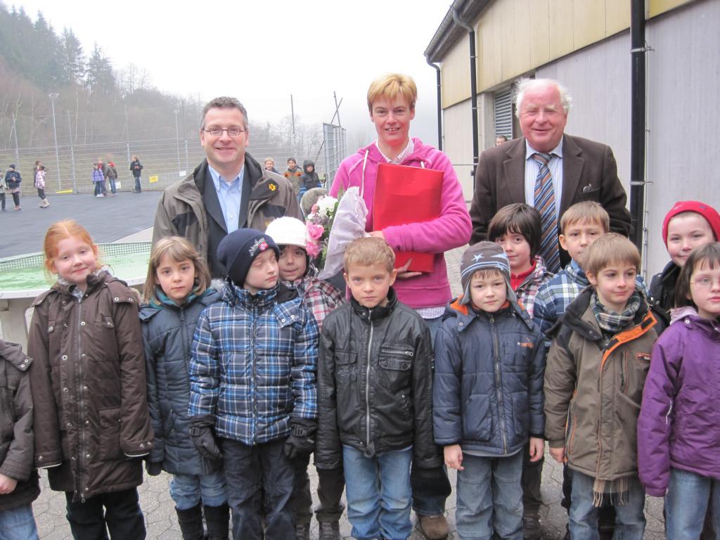 Beigeordneter Heinz Kugel (hinten rechts) und Ortsbürgermeister Philipp Thönnes gratulierten Petra Schallenberger zum Weltmeistertitel 2011. Die Jungen und Mädchen unserer Schule freuen sich mächtig. Foto: Benedikt Schmitt